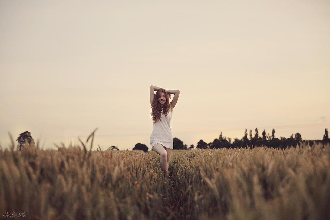 A beautiful young woman with green eyes and long brown curly hair, looking lovely in a corn field in summer