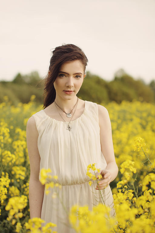 A beautiful English girl with pale skin, green eyes and long brown hair in a field of yellow rapeseed flowers in England.