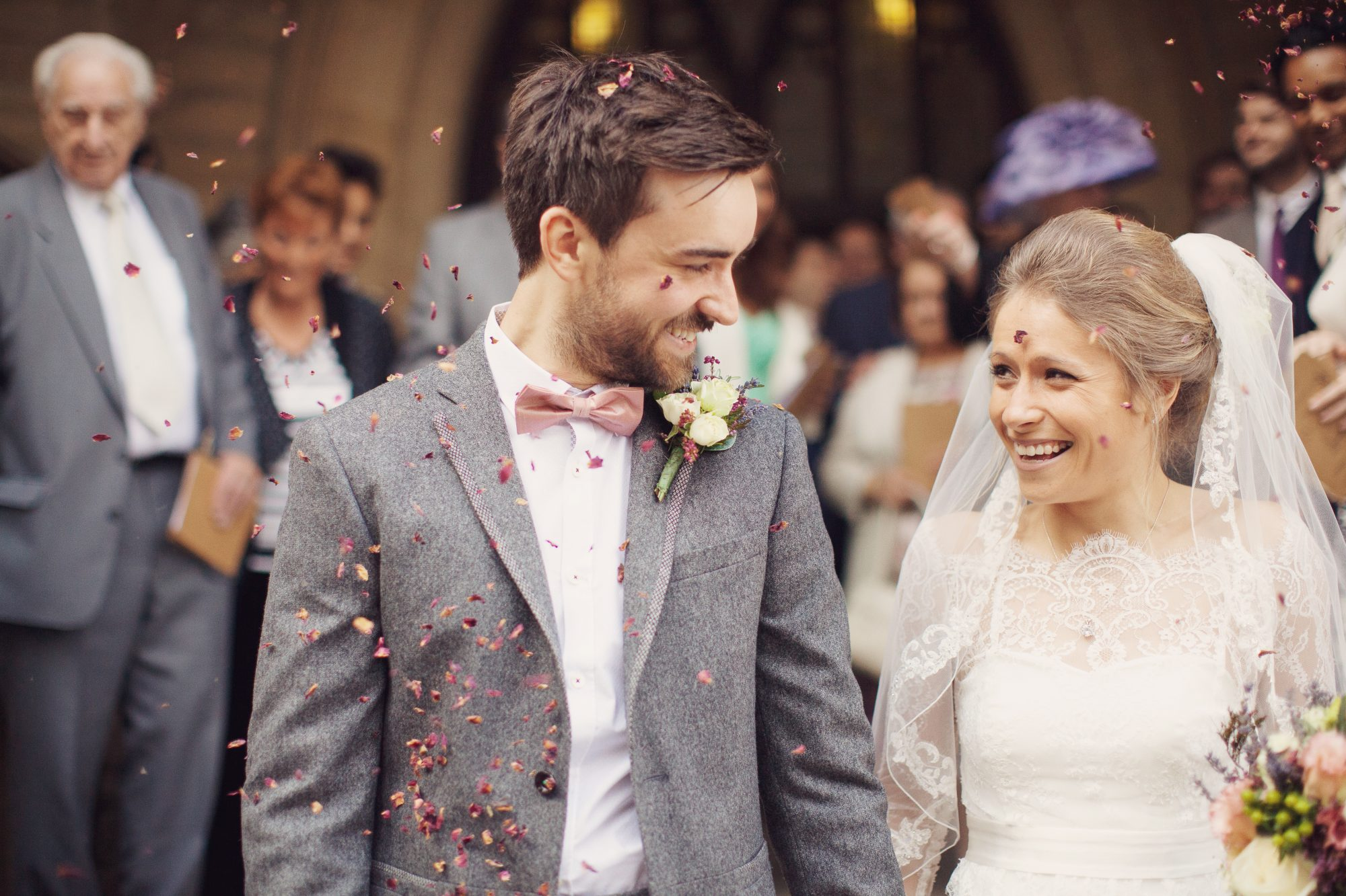 A beautiful newlywed couple walking through their red rose petal confetti throw at their wedding at St. John's Ranmoor Church in Sheffield