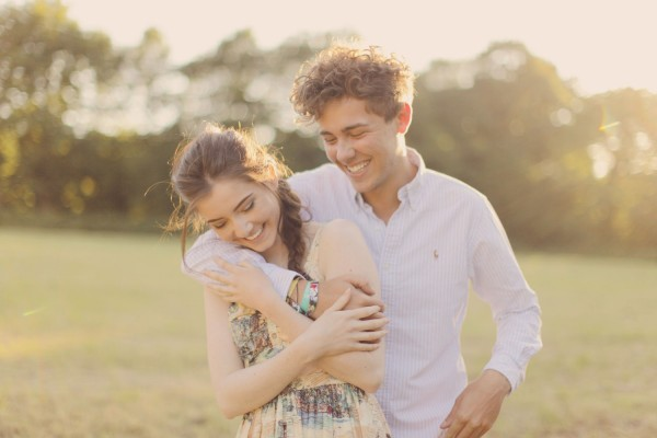 Romantic couple smiling in a field on the Peak District - engagement photoshoot