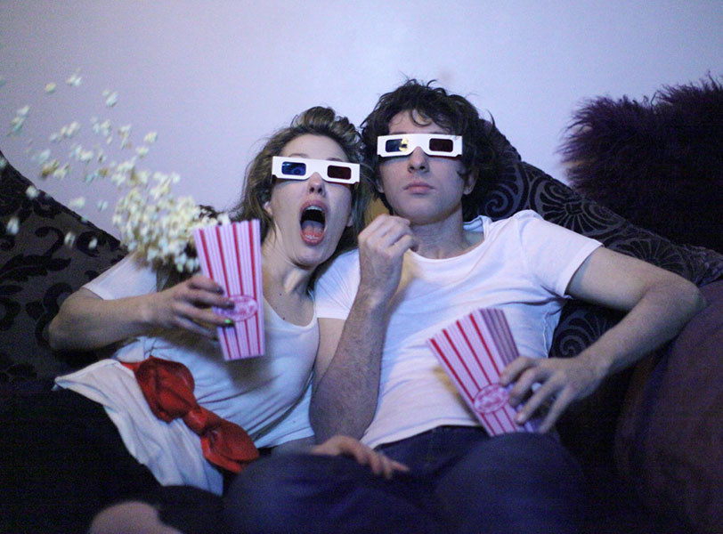 Funny photo of a cute couple watching a horror movie together with 3D glasses and popcorn at their unique engagement photoshoot in Sheffield