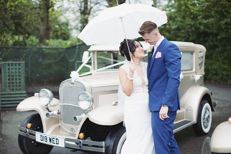A Ringwood Hall wedding in Chesterfield with the bride and groom by a vintage car by Sasha Lee Photography