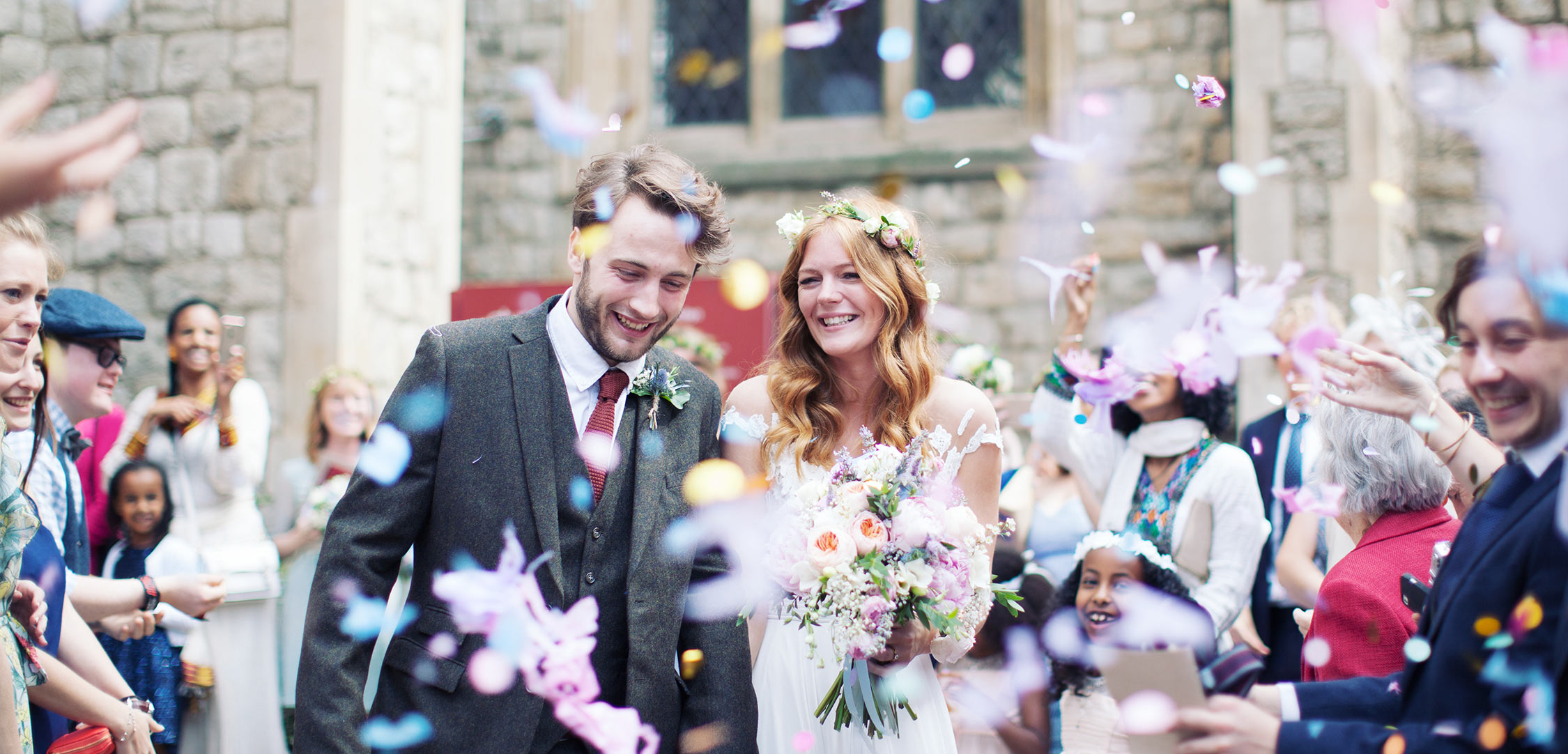 Beautiful natural wedding photography with a stunning bride and groom being showered with chunky confetti