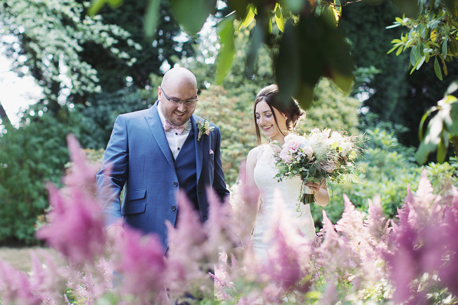 Beautiful, natural and romantic wedding photography at Sheffield Ecclesall garden venue Whirlowbrook Hall with a small wedding party and a photo of a gorgeous bride with brown hair and bright blue eyes and handsome bald groom by Sasha Lee Photography