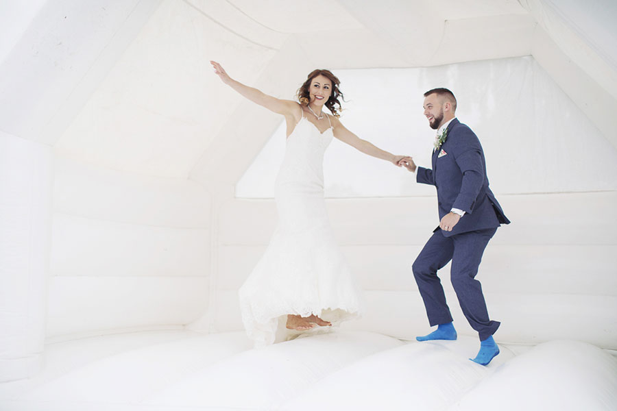 Beautiful natural candid wedding photography in Derbyshire Ilkeston home marquee garden venue photo of a white bouncy castle hire by Sasha Lee Photography
