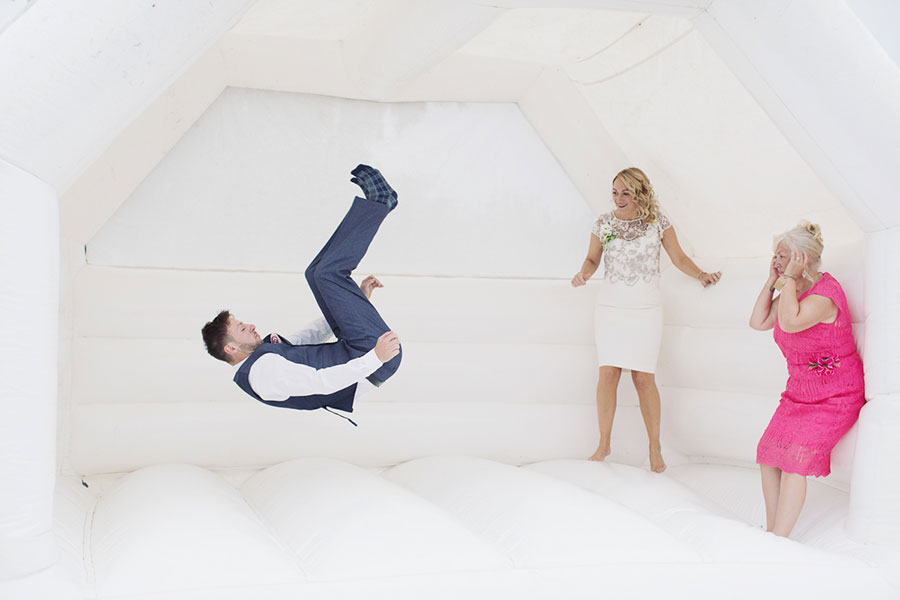 Beautiful natural candid wedding photography in Derbyshire Ilkeston home marquee garden venue photo of a fun white bouncy castle for hire
