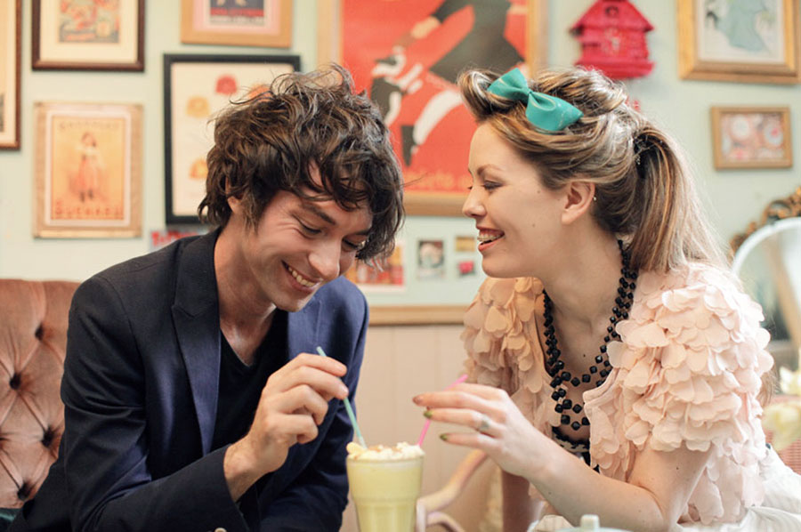A beautiful couple on their engagement shoot sharing a milkshake with burlesque fashion, in Cocoa Wonderland, Sheffield